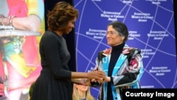 Тожикистонлик Ойниҳол Бобоназарова АҚШнинг биринчи хоними Мишель Обама қўлидан мукофотни олмоқда, Вашингтон, 2014 йилнинг 4 марти.
