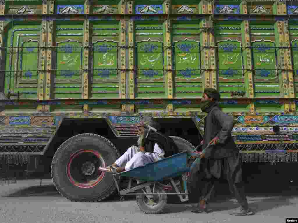 A teenage boy uses a wheelbarrow to push an elderly Pashtun man past a supply truck in Pakistan after traffic was halted at the Pakistan-Afghanistan border crossing in Chaman. (REUTERS/Naseer Ahmed)