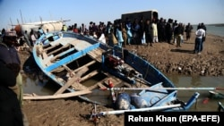 FILE: Pilgrims wait beside a boat after it capsized while carrying pilgrims to the shrine in the southern province of Sindh.
