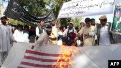 """Афганские студенты жгут американский флаг во время акции протеста против фильма """"Невинность мусульман"""". Афганистан, 19 сентября 2012 года."""