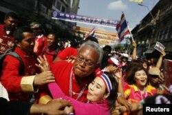 Сутхеп Тхаксубан, одетый в красное по случаю празднования Восточного Нового года, во время марша оппозиции по китайскому кварталу Бангкока. 1 февраля 2014 года