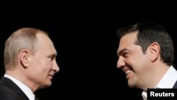 Greek Prime Minister Alexis Tsipras (right) welcomes Russian President Vladimir Putin in Athens on May 27.