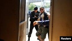 Полиция жер реформасына қарсылық акциясынан хабар таратпақ болған журналисті ұстап көлікке кіргізіп жатыр. Алматы, 21 мамыр 2016 жыл.