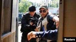 Полицейские задерживают журналиста, освещающего акцию протеста против земельной реформы. Алматы, 21 мая 2016 года.