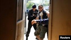 """Полиция қызметкерлері """"жер мәселесіне"""" қатысты қарсылық шеруінен хабар әзірлеп жүрген журналисті ұстап жатыр. Алматы, 21 мамыр 2016 жыл."""