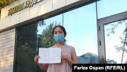 Азаматтық белсенді Фариза Оспан Шымкенттегі Еңбекші аудандық полиция басқармасының алдында наразылық білдіріп тұр.