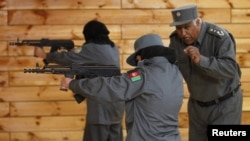 Female Afghan police officers with a commanding officer during a shooting exercise at a shooting range at the Afghan National Police Academy in Kabul in December 2012.