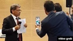 Үкімет делегациясының мүшесі Абдулло Рахнамо Тәжікстанда түрмеде отырған Махмадали Хаиттың хатын көрсетіп тұр. Варшава, 18 қыркүйек 2019 жыл.