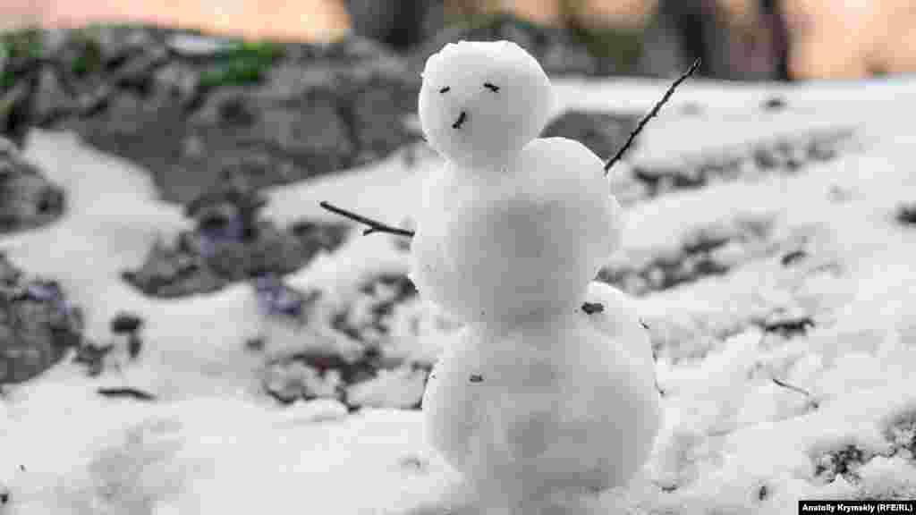 Туристы на скорую руку слепили маленького снеговичка