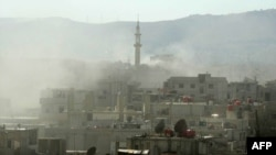 Smoke rises above buildings following what many say was a toxic gas attack by Syrian forces on the outskirts of Damascus on August 21.