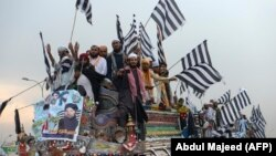 Supporters of the Islamist Jamiat Ulema-e-Islam (JUI-F) wave party flags atop a vehicle as they take part in an anti-government protest on October 31.
