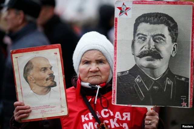 A supporter of the Russian Communist Party holds portraits of Vladimir Lenin (left) and Josef Stalin during a procession to mark Defender of the Fatherland Day in Moscow on February 23.