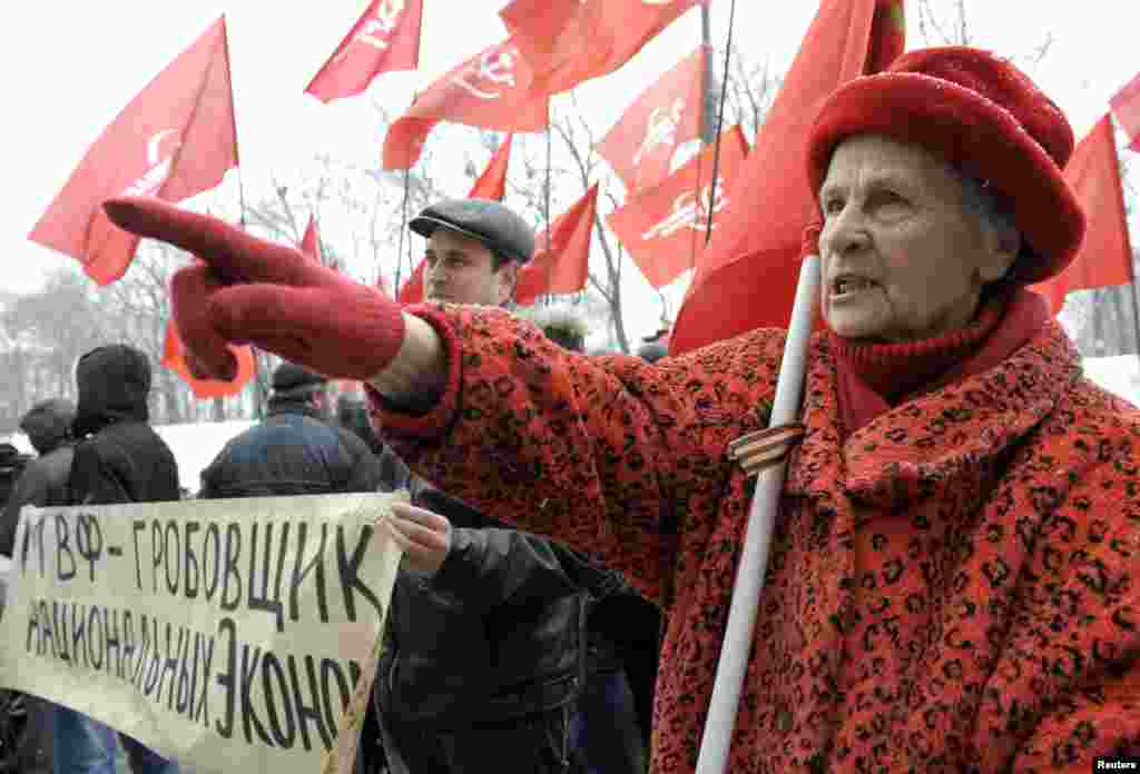 "Supporters of the Communist Party hold a rally protesting the arrival of a mission from the International Monetary Fund in Ukraine. The IMF is expected to hold talks with Kyiv on a $15 billion loan. The banner reads ""IMF -- A Mortician Of The National Economics."" (Reuters/Alexandr Kosarev)"