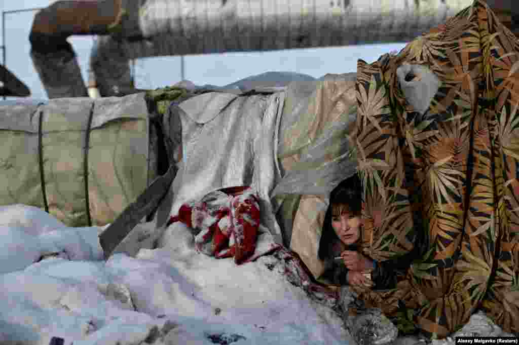 Galya, 29, looks out from a makeshift shelter. She is one of the thousands of people living rough in the city of Omsk.