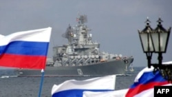 "Pro-Russian supporters welcome the missile cruiser ""Moskva"" to Sevastopol after participating in military operations against Georgia."