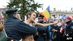 Police try to stop an activist of the Ukrainian feminist group Femen from protesting on St. Peter's Square at the Vatican on January 13.