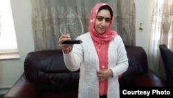 Afghanistan--Radio Azadi journalist Nazeefa Mahboobi displays award she received from local NGOs for her investigative reporting. April 2016.