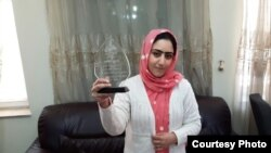 Radio Azadi journalist Nazeefa Mahboobi displays the award she received from local NGOs for her investigative reporting.