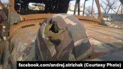 """Шлем, поврежденный осколком снаряда, на капоте сгоревшего """"уазика"""" в Песках"""