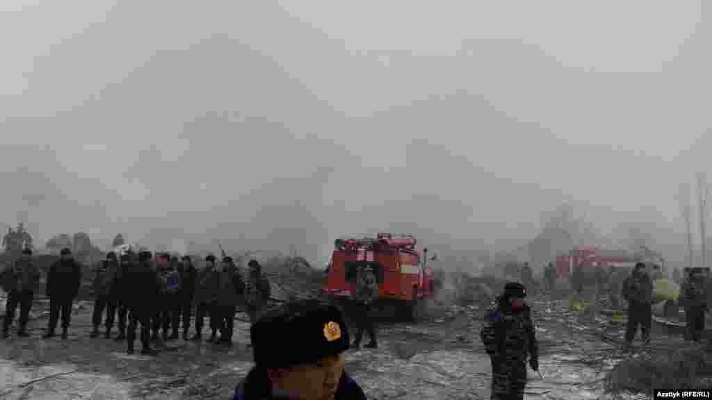 Пожарные и врачи скорой помощи на месте падения самолета.
