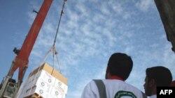 کارکنان هلال احمر ایران در حال بارگیری کشتی حامل کمک های دارویی و غذایی به مردم غزه. (عکس: AFP)