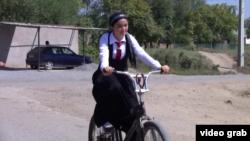 Велосипед менен мектепке бараткан окуучу кыз