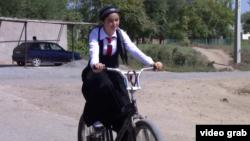 Велосипед теуіп келе жатқан оқушы қыз.