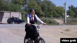 Школьница-таджичка в селе едет на велосипеде.