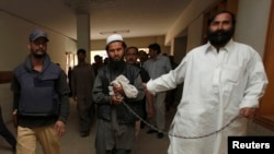 Pakistani Police escort a man through the halls of a court in Karachi.