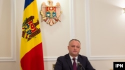A file photo of Moldovan President Igor Dodon with the country's current tricolor flag in the background.