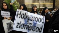 Женщины возле посольства Швеции в Иране держат в руках плакаты против показа фильма, насмехающегося над Пророком. Тегеран, 13 сентября 2012 года.