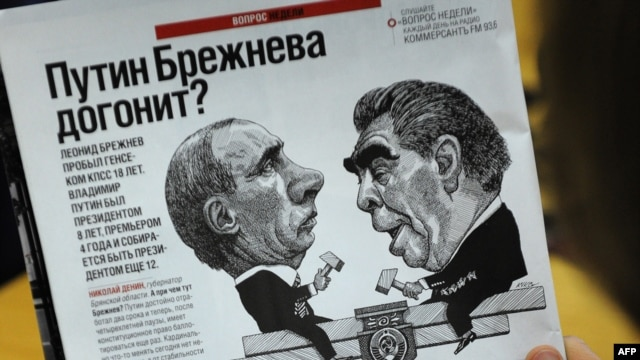 A man looks at a cartoon depicting Premier Vladimir Putin (left) and former Soviet leader Leonid Brezhnev in a magazine in Moscow.
