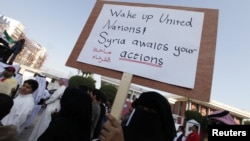 A protester in Bahrain holds a banner saying ''Wake up United Nations, Syria waits for your action'' as she protests outside the UN House in Manama on December 30.