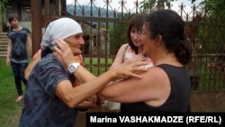 Biological mother Liana Khurtsidze (left) and adoptive mother Linda Stone embrace upon meeting in Dikhashkho, in western Georgia, on July 16.