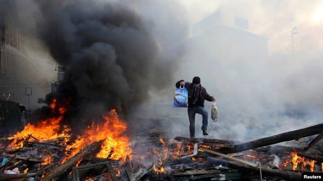 Ukraine -- A man walks amidst burning remains of fires at Independence square in Kyiv, February 21, 2014