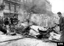 Горящие обломки автобусов и грузовиков, уничтоженных советскими танками. Протестующие использовали их в качестве баррикад, чтобы заблокировать подход советских военных под стены здания Чехословацкого радио в Праге, 1968 год