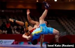 Казахстанский борец Мейрамбек Айнагулов (в синей форме) и Ри Се Ун из Северной Кореи. Джакарта, 21 августа 2018 года.