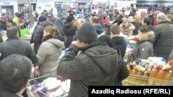 Люди, скупающие после девальвации маната продукты питания в супермаркете, ожидают очереди. Баку, 22 февраля 2015 года.