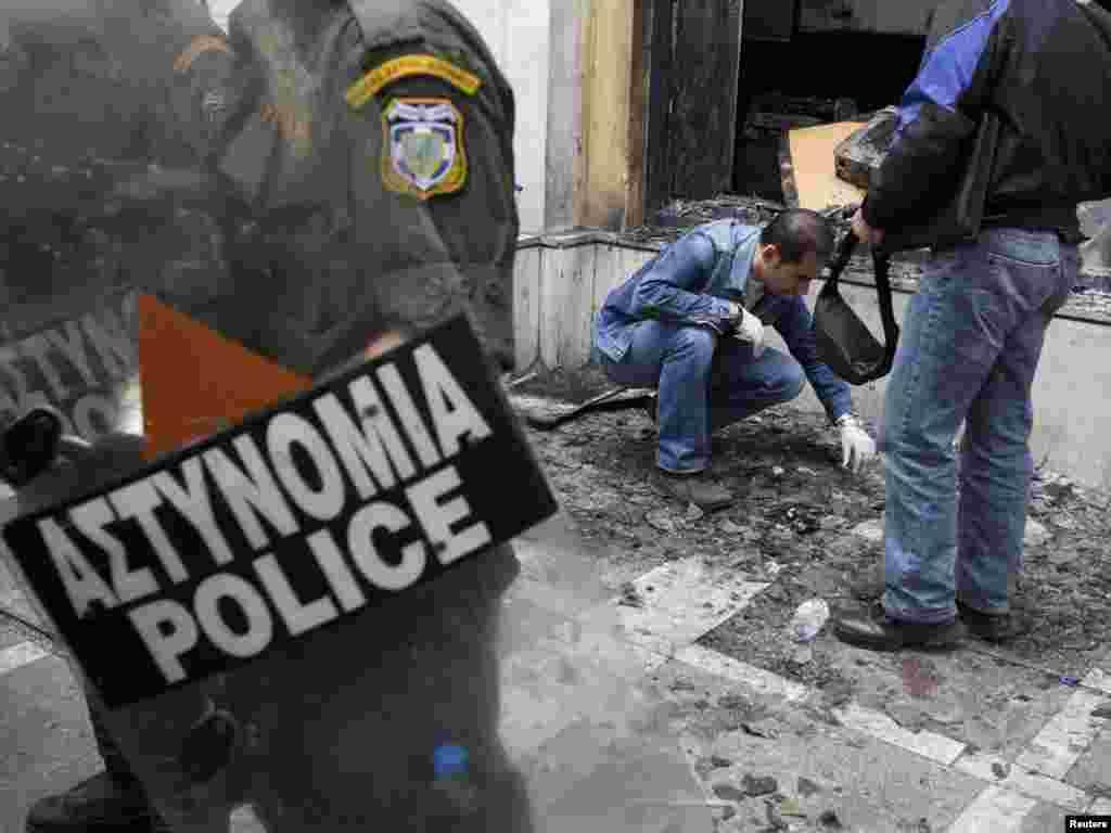 Грэцыя, Атэны: паліцыя побач з банкам, які быў падпалены.