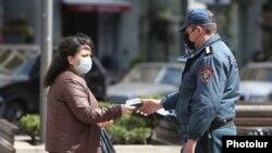Armenia -- A police officer enforcing a coronavirus lockdown checks a woman's documents, Yerevan, March 25, 2020.