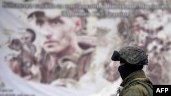 Un soldat rus în fața bazei militare ucrainene de la Perevalnoie, lîngă Simferopol, la 20 martie