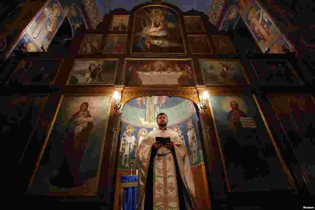 In Bosnia-Herzegovina, Serbian Orthodox Priest Bojan Glisic prays on the eve of Orthodox Christmas in the central Bosnian town of Zenica.
