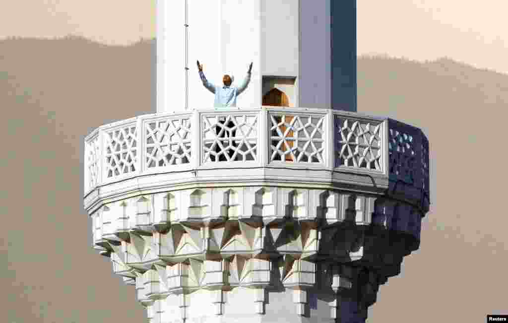 An imam issues the call to prayer from the marble minaret of a mosque.