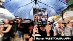 عکس در دست معترض هنگکنگی چین را به حزب نازی آلمان تشبیه کرده است