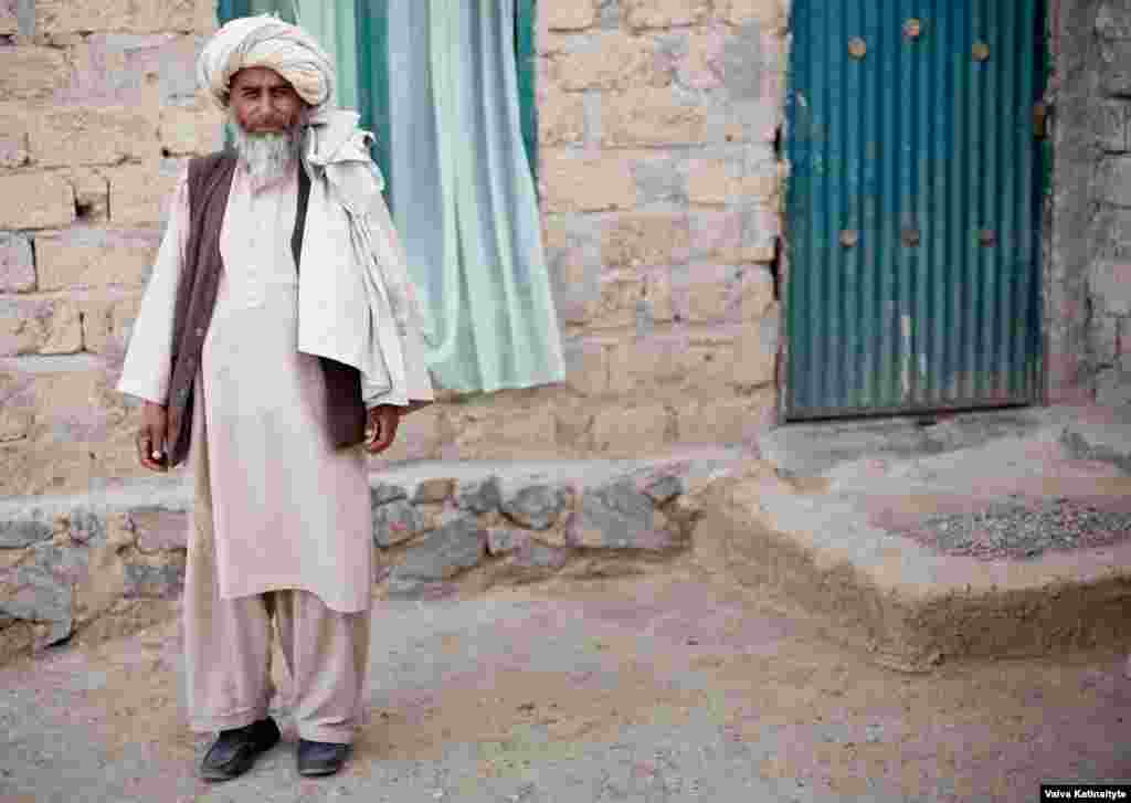 Haji Khanzada, a local elder, provides food and water for the returnees.