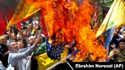 State organized demonstrators burn Israeli and U.S. flags to show their anger over the deaths of nearly 60 Palestinians along the Gaza border on Monday, during a protest outside the former U.S. embassy in Tehran, May 16, 2018. File photo