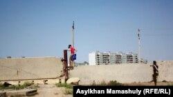 Некоторые желающие попасть в закрытый город Байконур перепрыгивают через бетонное ограждение со стороны села Акай. Кызылординская область, 14 июля 2013 года.
