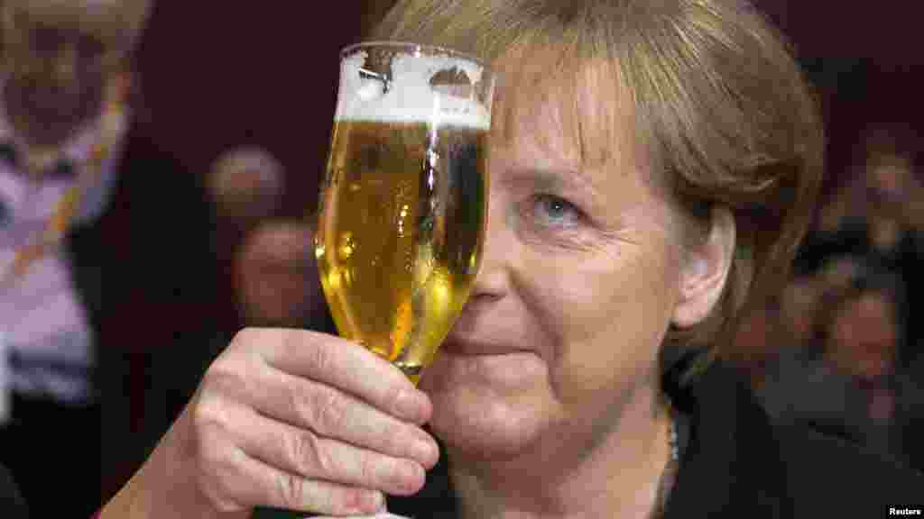 German Chancellor Angela Merkel toasts with a glass of beer during a Political Ash Wednesday meeting of the Christian Democratic Union (CDU) in Demmin on February 22. (REUTERS/Thomas Peter)