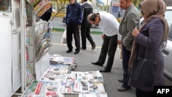 Iran -- People look at newspapers displayed on the ground outside a kiosk in Tehran, November 25, 2013