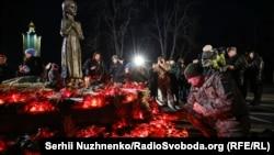 Люди кладуть колоски і хліб, запалюють свічки біля пам'ятника «Дівчинці з колосками», 23 листопада 2019 року